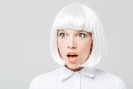 mouth opened: Closeup of amazed pretty young woman with mouth opened over white background