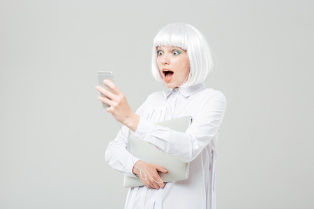 wondered: Wondered cute young woman with laptop listening to music from smartphone over white background