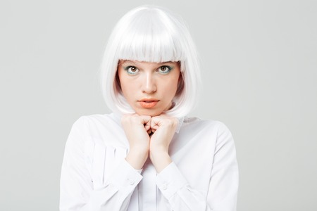 hesitation: Portrait of shy cute young woman with blonde hair over white background Stock Photo
