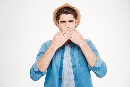 speechless: Handsome young man in blue shirt and hat covered his mouth by hands over white background