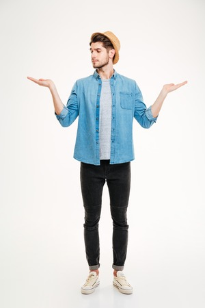 copyspace: Thoughtful young man standing and holding copyspace on both palms over white background