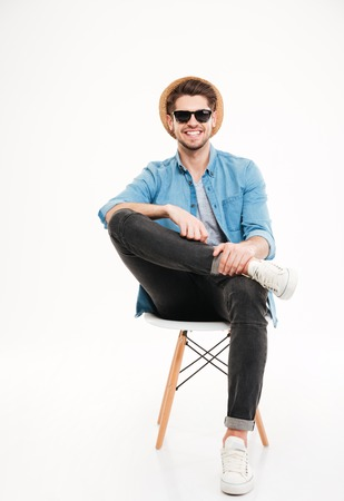 Cheerful relaxed young man in hat and glasses sitting on chair over white background