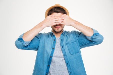 unsighted: Serious young man in blue shirt and hat covered his eyes by hands over white background Stock Photo