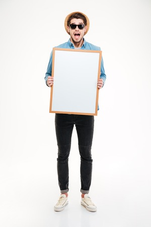 mouth opened: Amazed young man with mouth opened shouting and holding blank whiteboard over white background