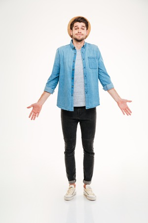 shrugging: Confused cute young man in jeans shirt standing and shrugging over white background