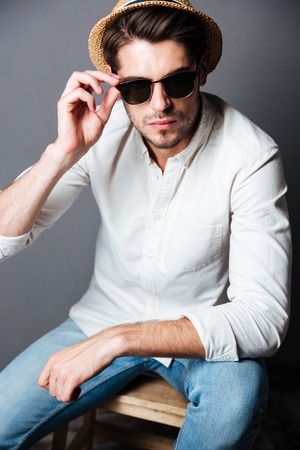 ccloseup: Fashion portrait of serious young man in white shirt, jeans, sunglasses and hat over grey background