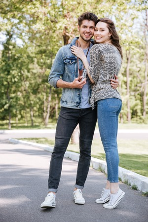 standing together: Portrait of a happy romantic couple having date outdoors in the park Stock Photo