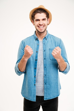 rejoices: Casual handsome young man rejoices isolated on the white background