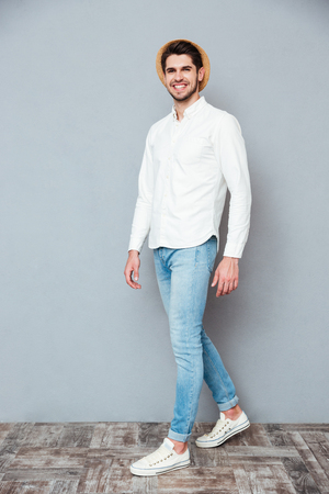 stylish men: Cheerful handsome young man in white shirt, jeans and hat smiling and walking over grey background