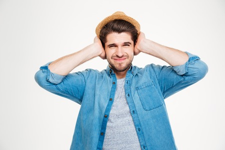 hands over ears: Frowning handsome young man covered ears by hands over white background