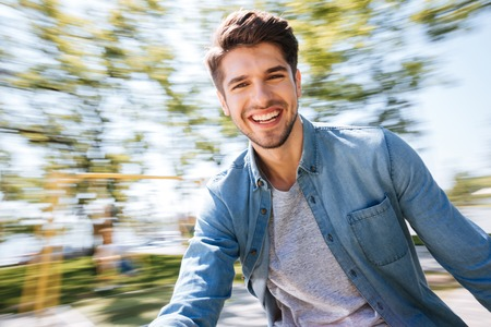 Giovane uomo bello felice divertendosi al parco all'aperto