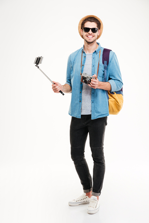 Cheerful young tourist with backpack, old photo camera and smartphone on selfie stick over white background Stock Photo
