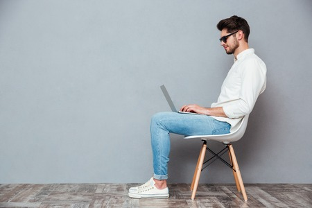 Profiel van de ernstige jonge mens in zonnebril die op stoel zitten en laptop over grijze achtergrond met behulp van