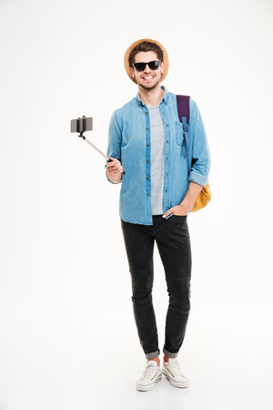 De volledige lengte van de glimlachende jonge mens met rugzak en mobiele telefoon op selfie plakt over witte achtergrond