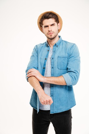 rolling up: Serious handsome young man standing and rolling up his sleeves over white background Stock Photo