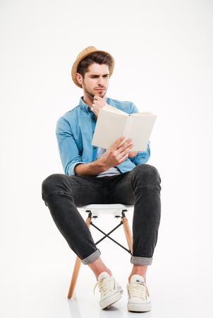Concentrado guapo joven en sombrero sentado y leyendo un libro sobre fondo blanco