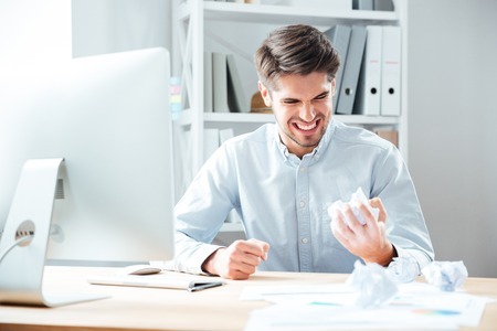 broken contract: Mad annoyed young businessman working and crumpling paper in office Stock Photo