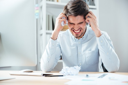 job deadline: Aggressive angry young businessman holding crumpled paper sitting at his workplace Stock Photo