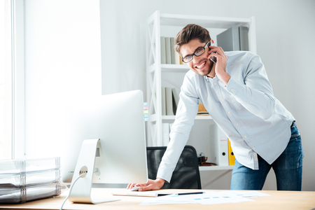 Smiling young businessman in glasses using computer and talking on mobile phone Standard-Bild