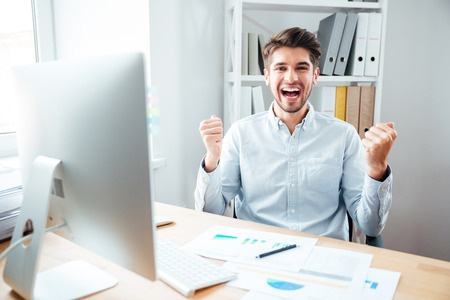 toiling: Cheerful excited young businessman sitting and celebrating success in office