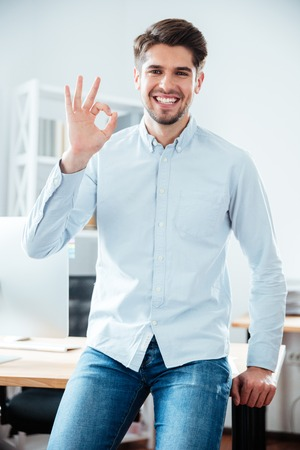 Portrait of smiling young businessman standing and showing ok sign Stock Photo