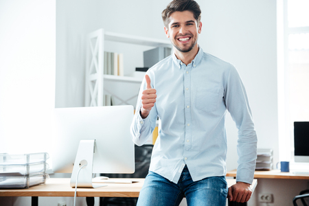 Cheerful young businessman standing and showing thumbs up in office