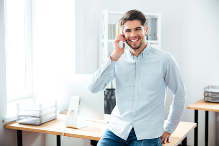 enterprising: Cheerful young businessman standing and talking on mobile phone in office Stock Photo