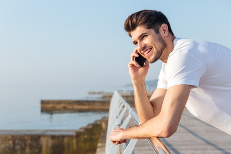 sund: Happy young man in white t-shirt talking on mobile phone outdoors Stock Photo