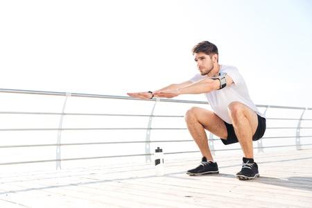 en cuclillas: Young handsome sportsman doing squatting exercises outside at the pier Foto de archivo