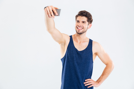 barbel: Happy young man athlete making selfie using mobile phone over white background