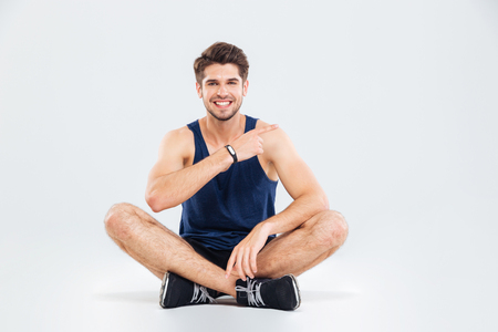 legs crossed: Smiling young fitness man sitting with legs crossed and pointing away over white background Stock Photo