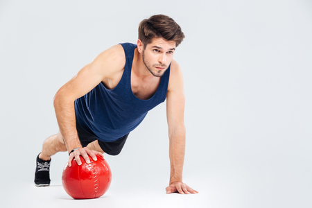 Full length portrait of a sports man workout with fitness ball isolated on a gray background