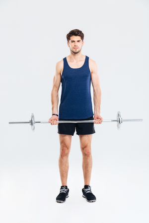 ful: Ful length of serious young man athlete standing and holding barbell over white background Stock Photo
