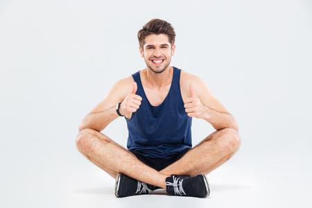 fitness joven feliz que se sienta con las piernas cruzadas y mostrando los pulgares hacia arriba sobre fondo blanco