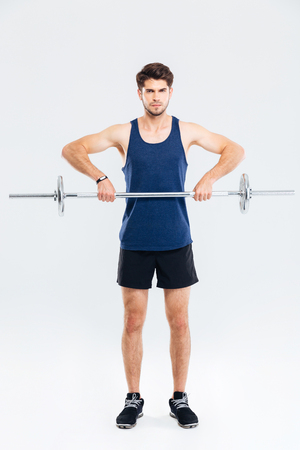 well build: Full length of handsome young sportsman training and lifting barbell over white background Stock Photo