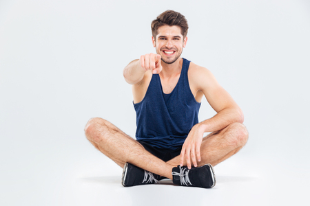 choise: Cheerful young sportsman sitting with legs crossed and pointing on you over white background