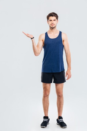 copyspace: Full length portrait of handsome confident attractive young sportsman holding copyspace on the palm over gray background Stock Photo