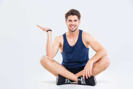 copyspace: Happy young athletic man sitting with legs crossed and holding copyspace on palm over white background