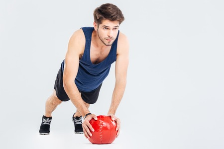Handsome young man athlete doing push ups on red ball over white background