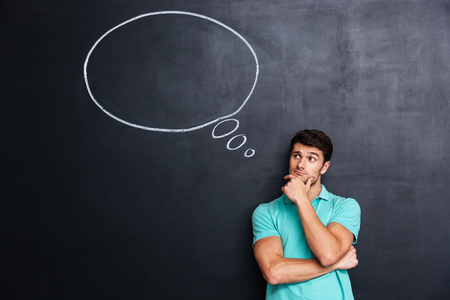 Pensive attractive young man with thinking bubble on blackboard background Stockfoto