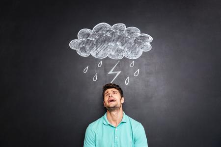 Desperate déprimé jeune homme debout et pleurant sous raincloud avec la foudre et la pluie tiré sur fond tableau Banque d'images