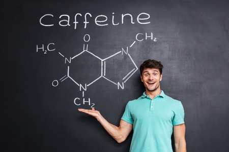 caffeine molecule: Cheerful young scientist showing chemical structure of caffeine molecule drawn on chalkboard background
