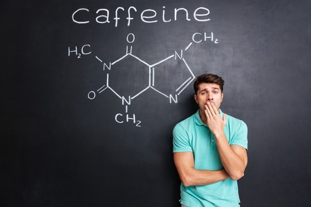 chemical structure: Tired sleepy young man yawning over blackboard background with drawn chemical structure of caffeine molecule