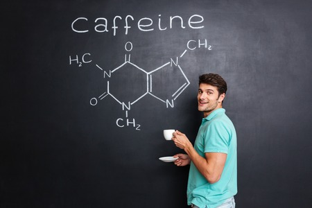 caffeine molecule: Happy young scientist standing over chemical structure of caffeine molecule drawn on chalkboard background and drinking coffee