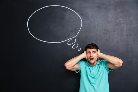 hands over ears: Shocked stressed young man with mouth opened covered ears by hands over chalkboard background Stock Photo