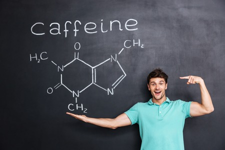 caffeine molecule: Cheerful young teacher standing and pointing on chemical structure of caffeine molecule drawn on chalkboard background