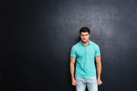irritate: Angry irritated young man stnding and looking away over chalkboard background