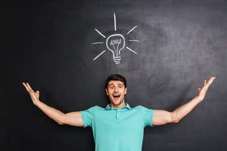 express feelings: Smiling excited young man standing and having an idea over chalkboard background Stock Photo