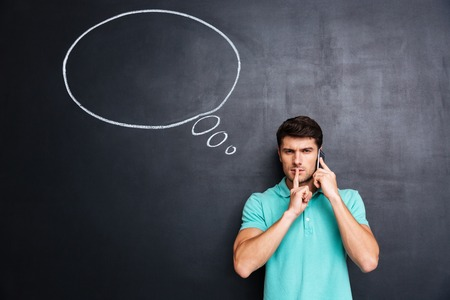 Handsome young man talking on cell phone and showing silence gesture with thinking bubble on chalkboard background