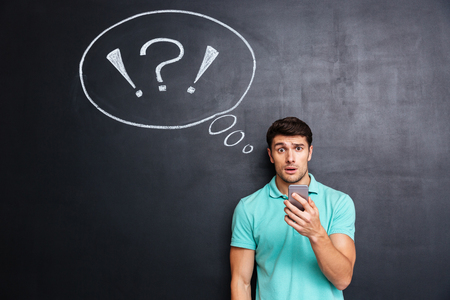 mobile sms: Amazed puzzled young man stanading and using cell phone over chalkboard background